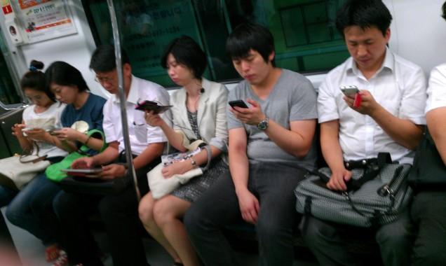 De reizigers in de metro in Seoul houden van hun mobiele apparaten.